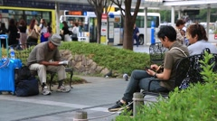 People sitting on the bench and using smart phone and reading books Stock Footage