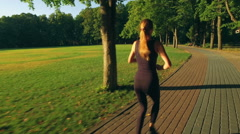 Runner woman running in park exercising outdoors Stock Footage