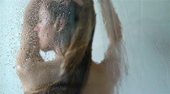Young slim woman taking a shower and washing her hair. Slow Motion. Stock Footage