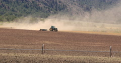 Hot desert mountain valley tractor dusty farm down DCI 4K Stock Footage
