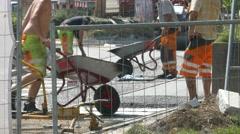 4K Construction Roadwork Hot porous Asphalt is applied loading in wheelbarrow Stock Footage