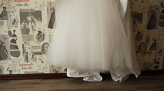 Wedding dress hanging on a hanger to the wall, a bride preparing for the wedding Stock Footage