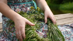 Girl makes a wreath of grass flowers  Stock Footage