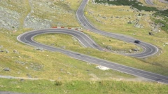 Difficult road with many serpentines, car going up in the mountains Stock Footage