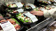 Woman selecting Greek salad inside Costco store at seafood department. Stock Footage
