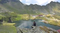 Young man sitting on the rock takes photos of the lake surrounded by mountains Stock Footage