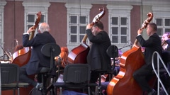 Men playing violoncello, outdoor concert Stock Footage