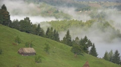 Lonely house on spring meadow, mist over green mountain, splendid countryside  Stock Footage