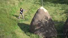 Hard working farmer cut down the grass in traditional way near haystack Stock Footage