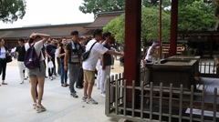 People throwing coins and praying for their wishes at Dazaifu shrine in Fukuoka Stock Footage