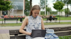 Student answers her cellphone while studying on laptop Stock Footage