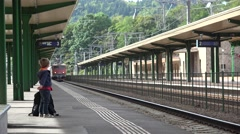 Little child waiting in railway station, boy waving his hand to the coming train Stock Footage