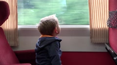 Tired child in the train looking on the window and singing Stock Footage