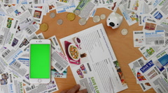 Top shot of man cutting coupon with various coupons and money background Stock Footage