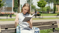 Absorbed schoolgirl sitting on the bench and reading a book Stock Footage