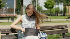 Student studying on laptop and drinking water while sitting on the bench Stock Footage