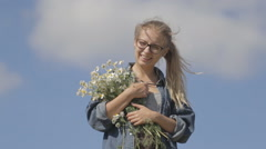 Girl with a bouquet of daisies on a background of blue sky Stock Footage