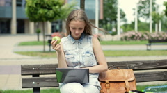 Pretty student eating apple and studying on laptop while sitting on the bench Stock Footage