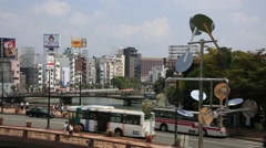 Cityscape of Fukuoka which has cars on the bridge and people walking Stock Footage