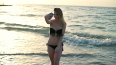 Young beautiful girl in swimwear smiling, making selfie at beach, sea background Stock Footage