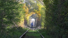 Man walking away on abandoned railway under autumn colored trees tunnel Stock Footage
