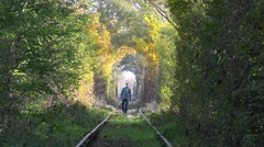 Young man coming on abandoned railway, beautiful autumn trees tunnel Stock Footage