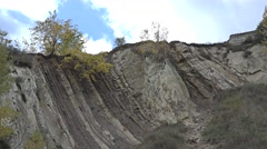 Autumn trees grown on rocky cliff, white fluffy clouds on serene blue sky Stock Footage