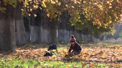 Happy child playing with parent with fallen leaves on beautiful autumn alley Stock Footage