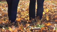 Couple of lovers feet walking on fallen autumn leafs, romantic stroll Stock Footage