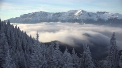 Splendid landscape of snowed trees, mountains and white fluffy clouds motion Stock Footage