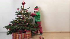 Funny elf arrange ornaments in Christmas tree, happy child waiting Christmas Stock Footage