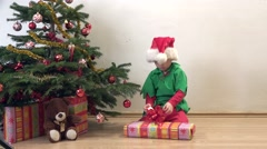 Amusing elf anxious loose present close Christmas tree, lovely child celebrate Stock Footage