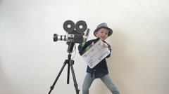 Funny child holding a clapboard, little director having fun, old camera Stock Footage