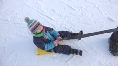 Adult pulling impromptu sledge with a happy child on fresh white snow Stock Footage