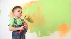 Happy child holding the paint roller,portrait of smiling kid love the job Stock Footage