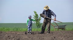 Grandfather and grandson plant a tree together, remove the gap generation Stock Footage