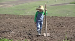 Funny child with a farmer hat hold a hoe, kid gardening  Stock Footage