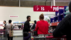 People line up for waiting to pick up their medicine inside Costco pharmacy Stock Footage