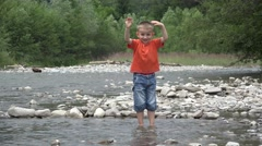 Happy child playing in a mountain river, kid splashing water with hands and feet Stock Footage