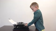Little child typing at old typewriter, reading the paper, the story of my life Stock Footage