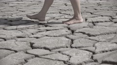 Feet walking on arid cracked soil, barefoot going on dry ground, conceptual Stock Footage