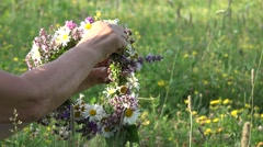 Hands arrange flower crown outdoor, beautiful green spring Stock Footage