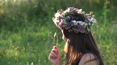 Woman with flower crown on her head playing with a daisy flower in a sunny day Stock Footage
