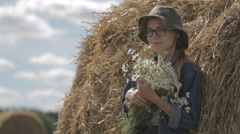 Girl in a hat with a bouquet of flowers is at stack of straw Stock Footage