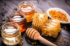 Honey in jar with honey dipper on black stone background Stock Photos