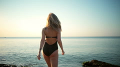 Young beautiful girl in swimwear smiling, fleeing in sea. Slow motion. Stock Footage