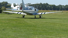 Sport plane with propeller rides across the field of green grass at airport Stock Footage