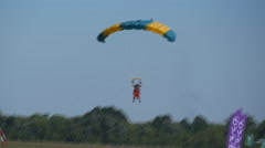 Two people flying on a parachute at blue sky and landing on grass of airport Stock Footage