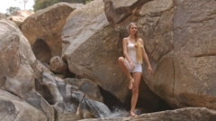 Blond Girl Stands in Yoga Tree Pose by Waterfall Stock Footage
