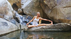 Blond Girl from Pose Half-Lotus Bends to Foot on Stone Stock Footage